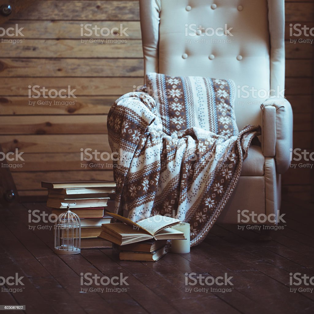 Stack of books with warm plaid on chair stock photo