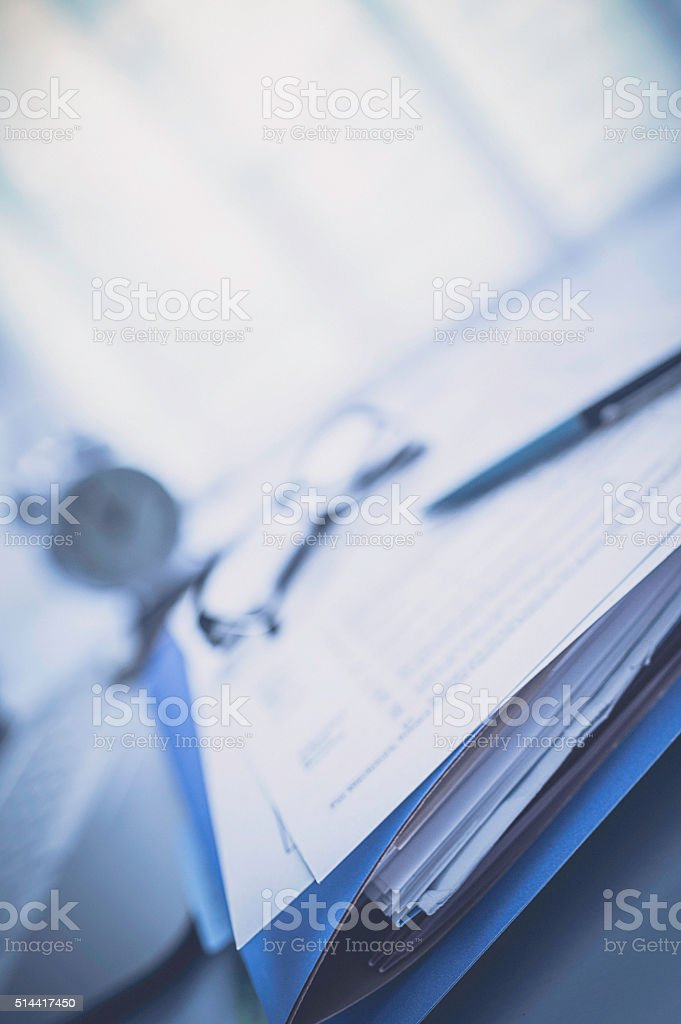 Stack of business paperwork in folders with pen in office stock photo