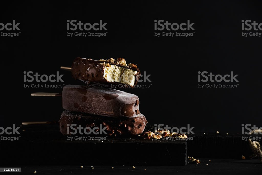 Stack of chocolate dipped popsicles with chipped nuts on dark stock photo