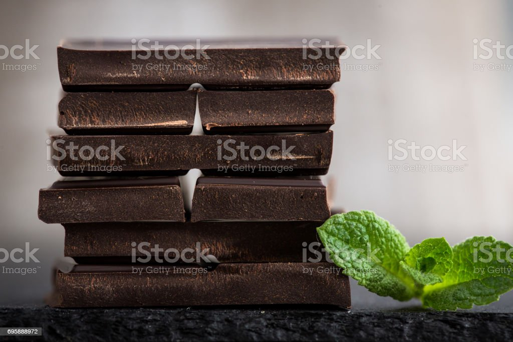Stack of chocolate slices with mint leaf. dark chocolate over wooden background, selective focus stock photo