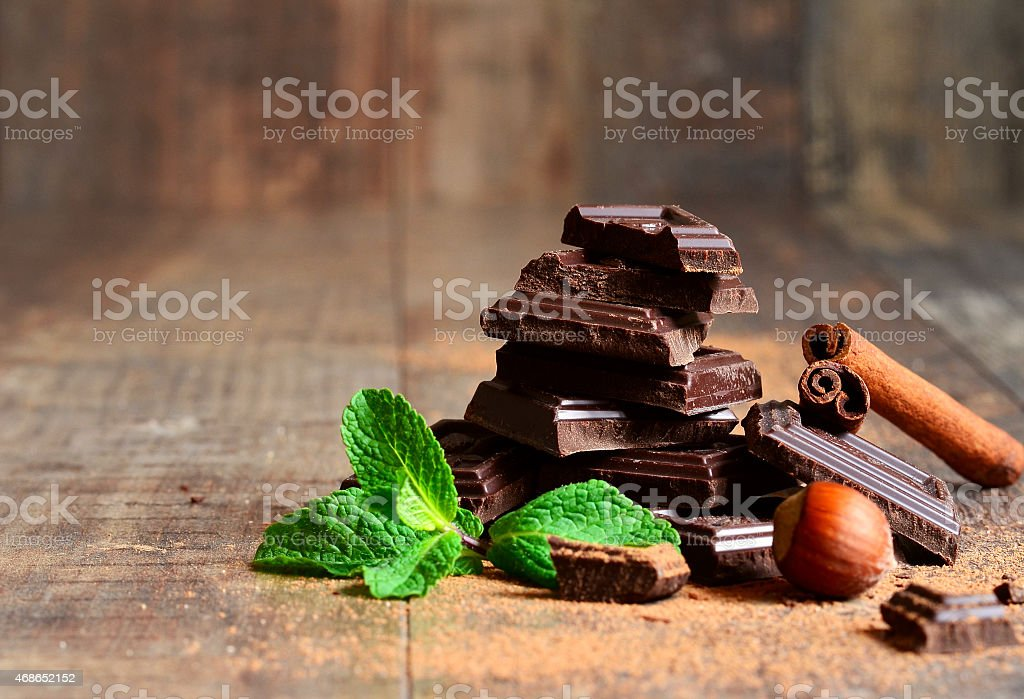 Stack of chocolate slices with mint leaf,hazelnut and cinnamon. stock photo