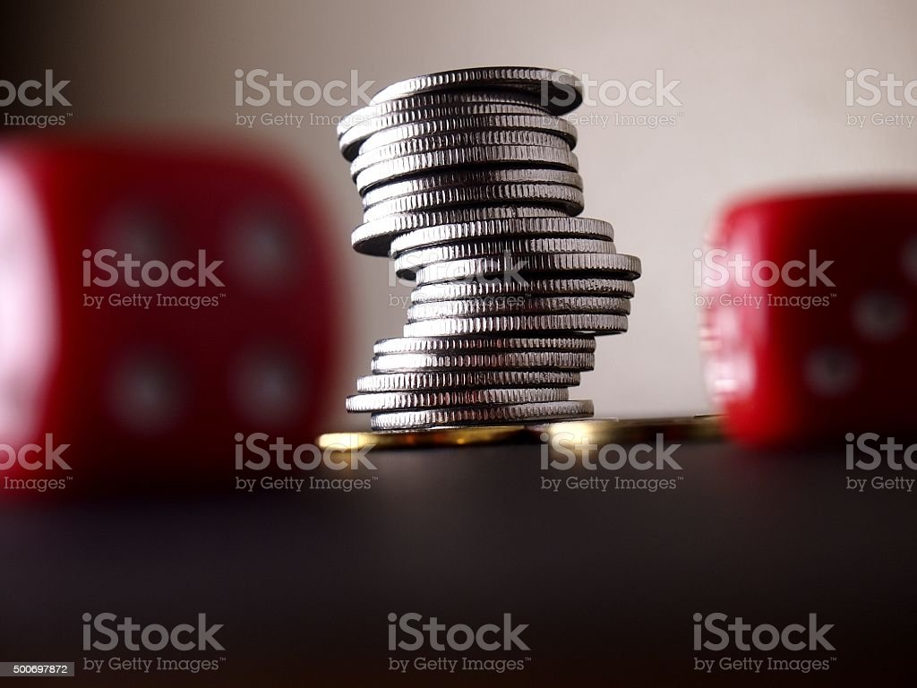 Stack of coins and two red dice stock photo