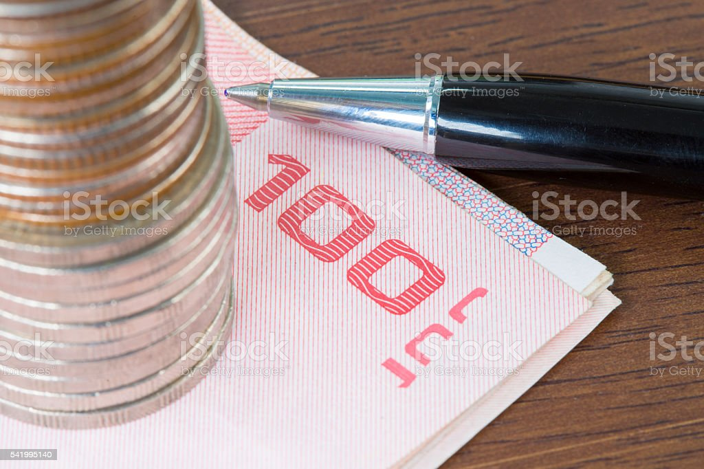Stack of coins on bill and ballpoint pen on wooden stock photo