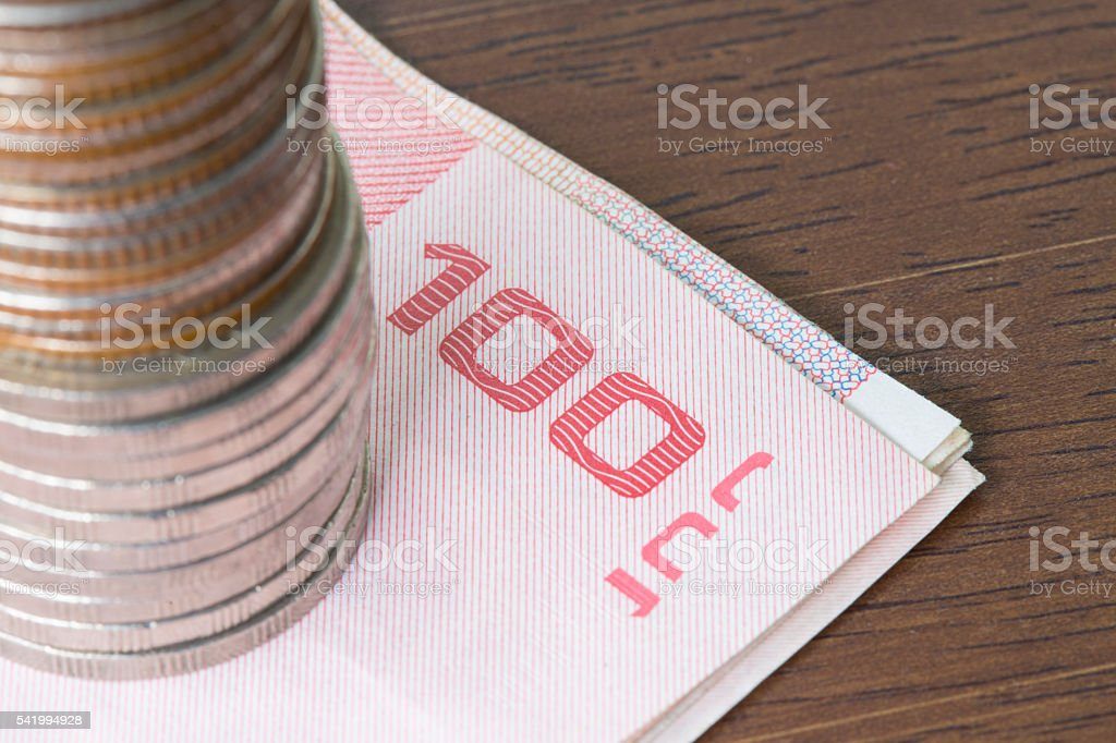 Stack of coins on bill on wooden table. stock photo