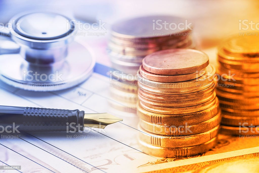 Stack of coins with a fountain pen and a stethoscope. stock photo