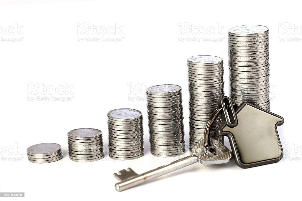 Stack of coins with house shape key on white background stock photo