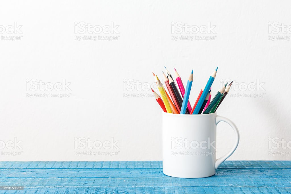Stack of colored pencils in a glass on wooden background stock photo
