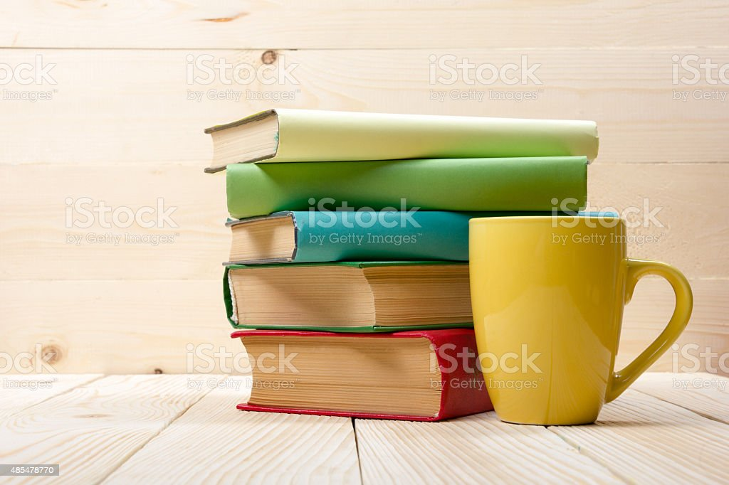 Stack of colorful books and cup on wooden table. stock photo
