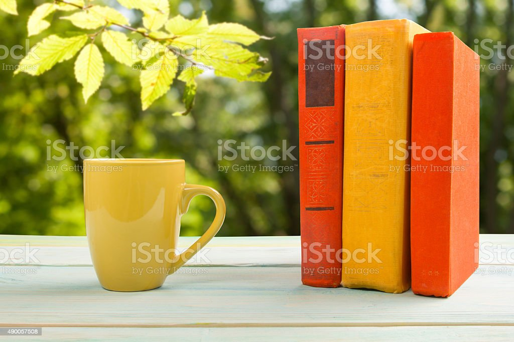 Stack of colorful books and cup on wooden table stock photo