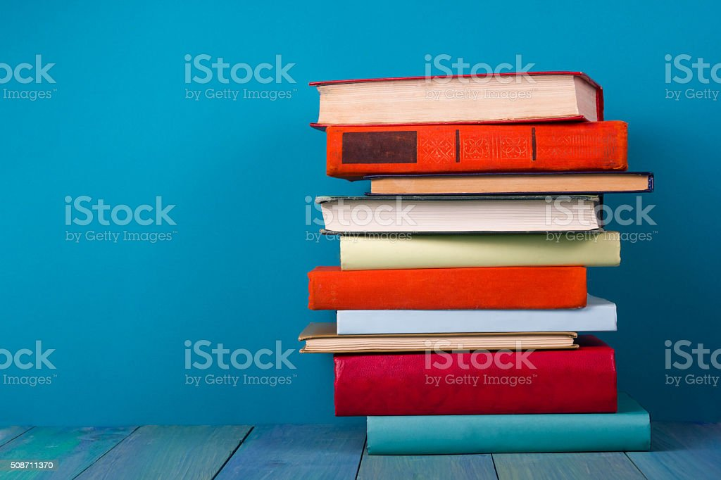 Stack of colorful books, grungy blue background, free copy space stock photo