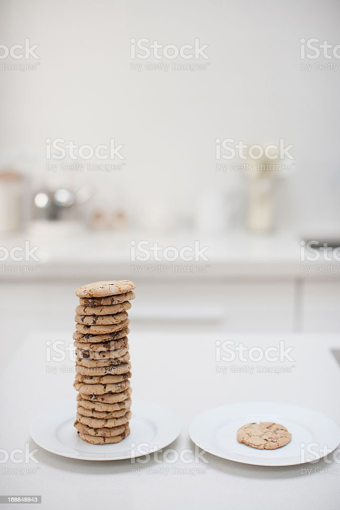 Stack of cookies on plate next to single cookie on plate stock photo