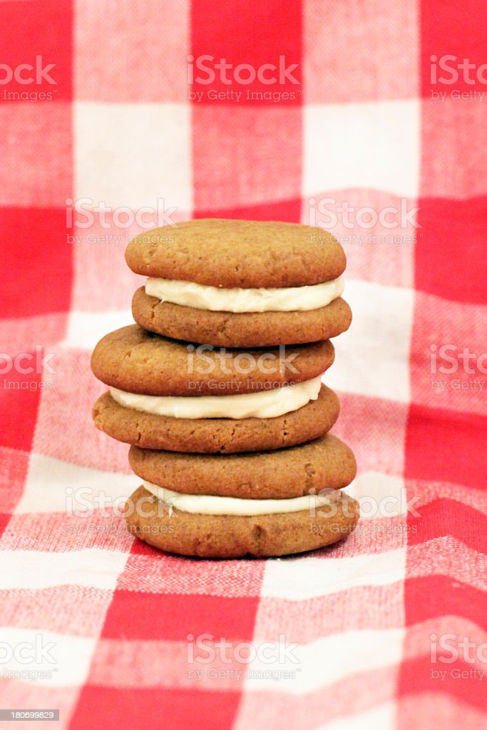 Stack of Cute Vanilla Sandwich Cookies on Checkered Tablecloth stock photo