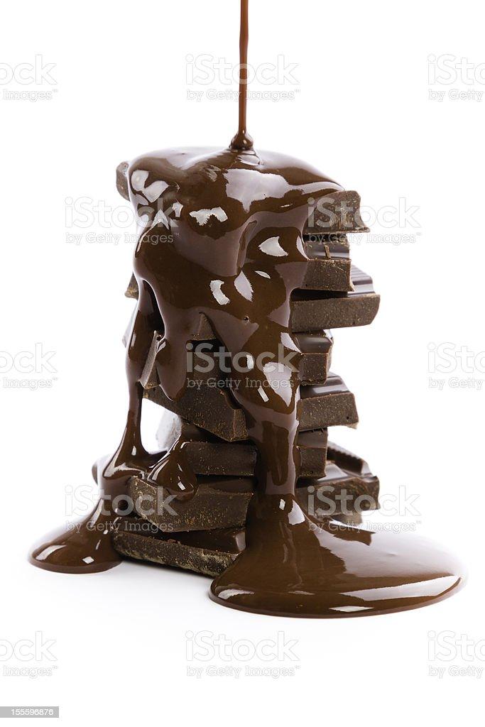 stack of dark chocolate pieces with liquid chocolate stock photo