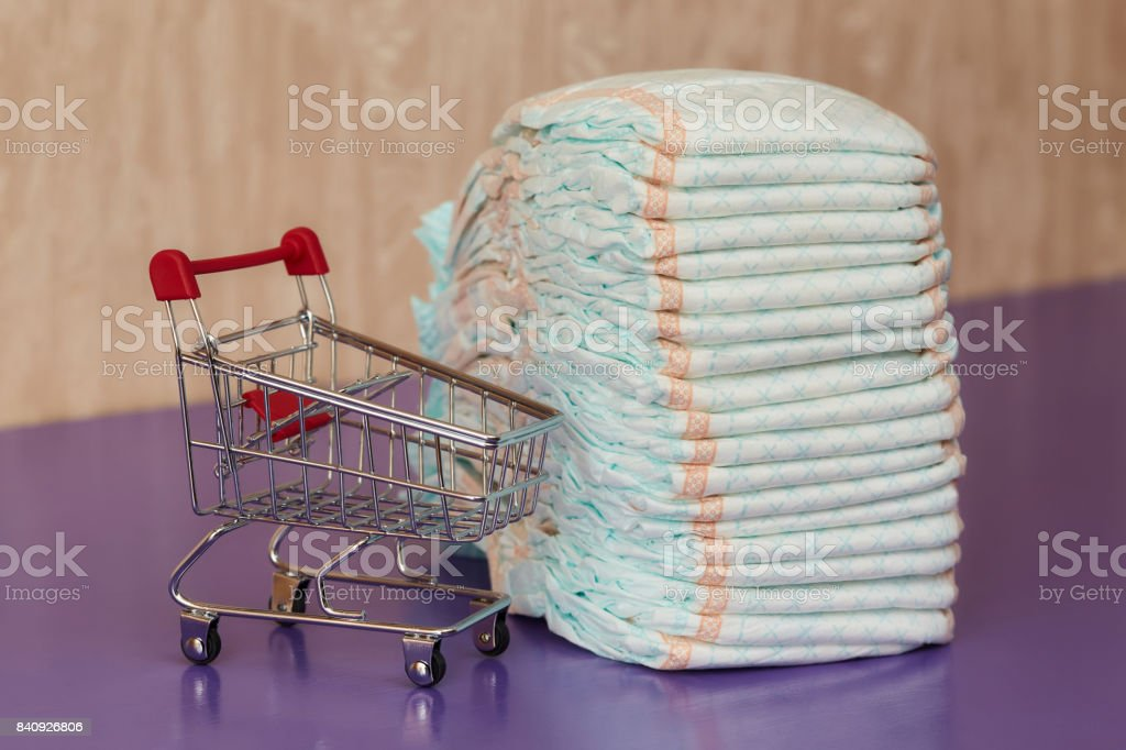 Stack of diapers or nappies and mini shopping cart, concept stock photo