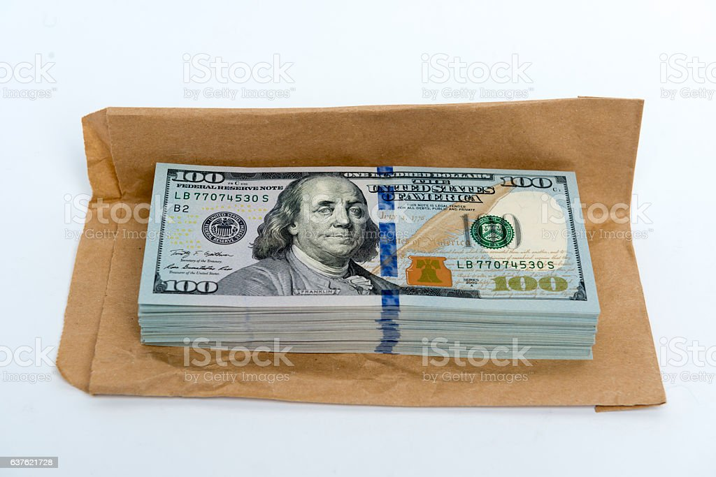 Stack of dollar banknotes and brown envelope stock photo