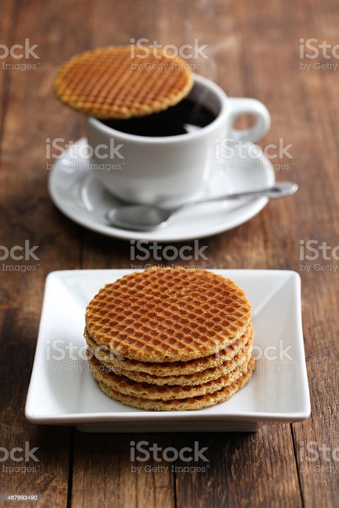 A stack of Dutch stroopwafels on a white plate with coffee stock photo