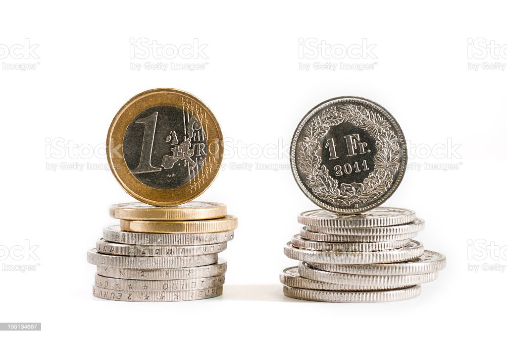 Stack of euros next to stack of francs stock photo