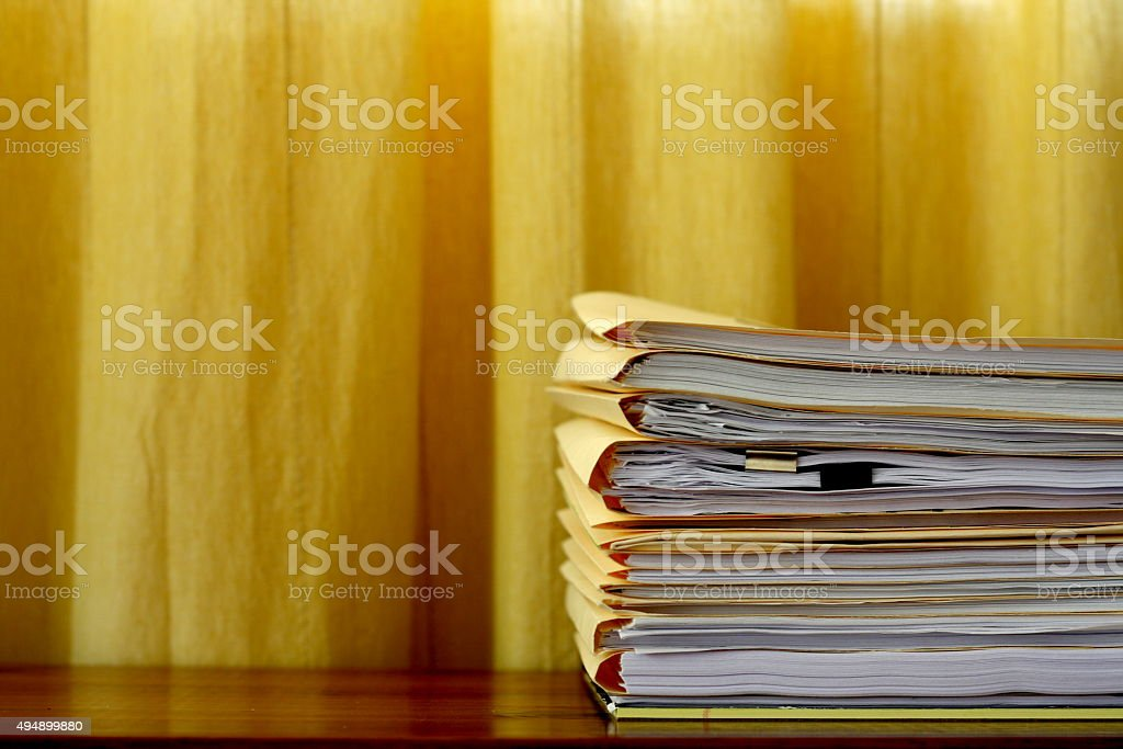 Stack of File Folders on a Wooden Desk stock photo