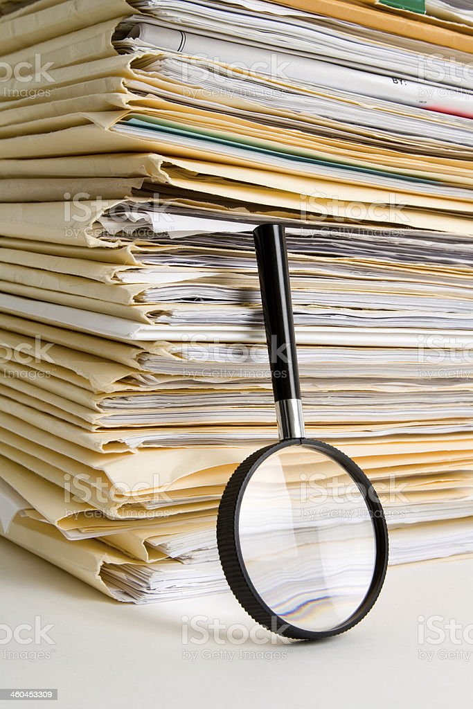 A stack of files with a magnifying glass beside them stock photo