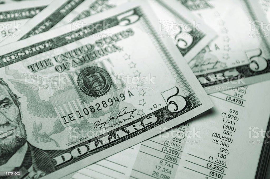 Stack of five dollar bills on top of a financial report. royalty-free stock photo