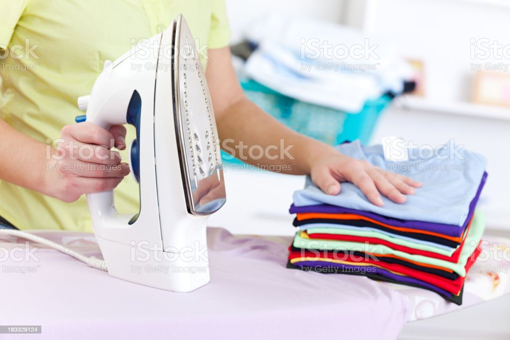 Stack of folded clean ironed clothes on an ironing board royalty-free stock photo