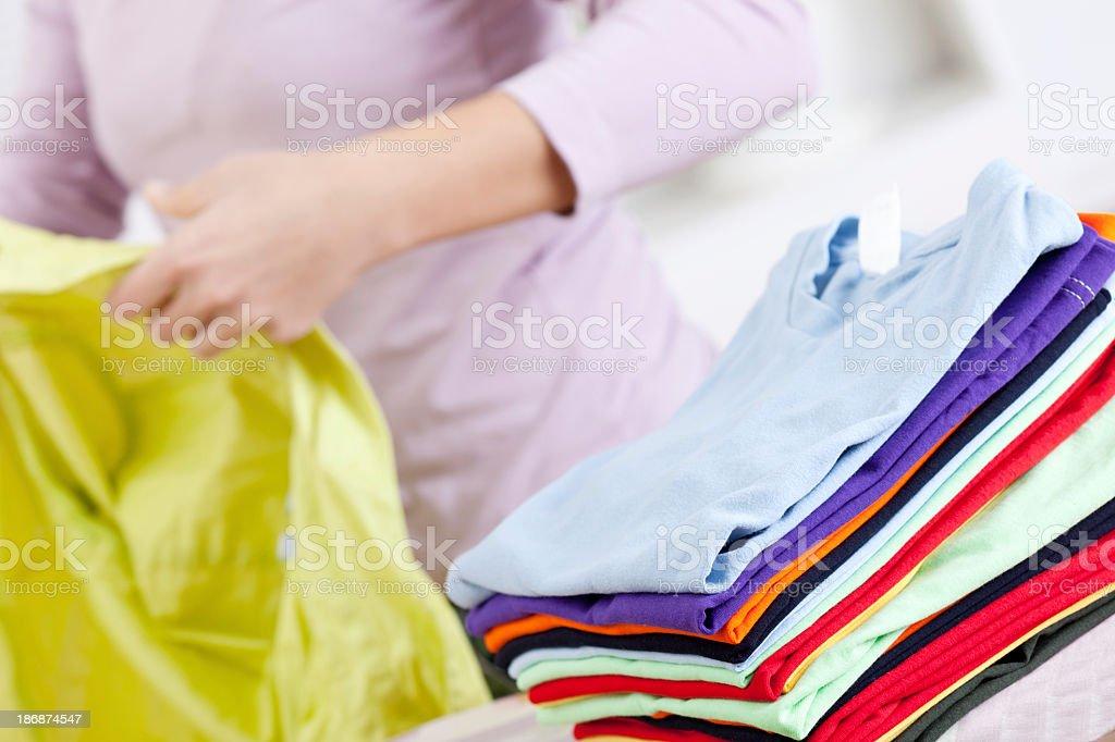 Stack of folded clean ironed clothes on an ironing board stock photo
