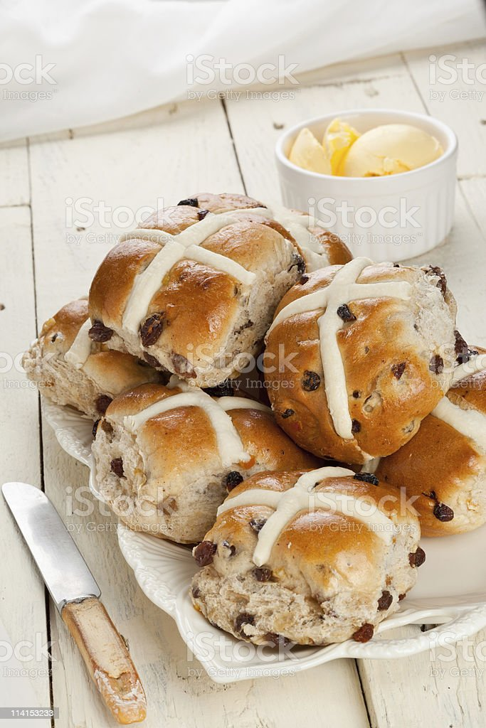 Stack of fresh hot cross buns with ramekin of butter stock photo