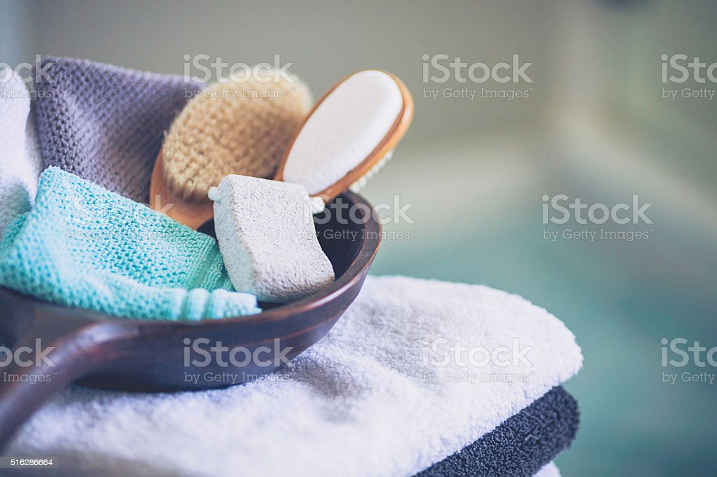 Stack of freshly laundered towels with wooden bowl and accessories stock photo