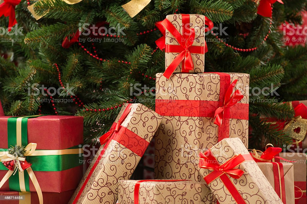 Stack of gift boxes under Christmas tree stock photo