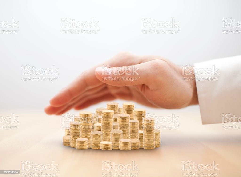 Stack of golden coins covered by hand. Savings protection concept stock photo