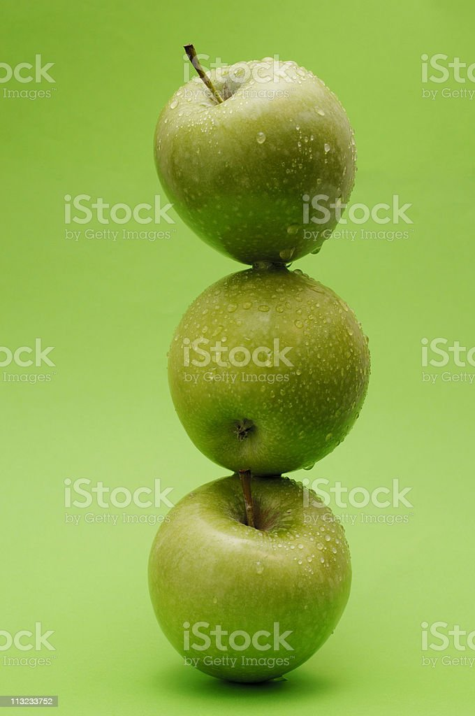 stack of granny smith apples against green royalty-free stock photo