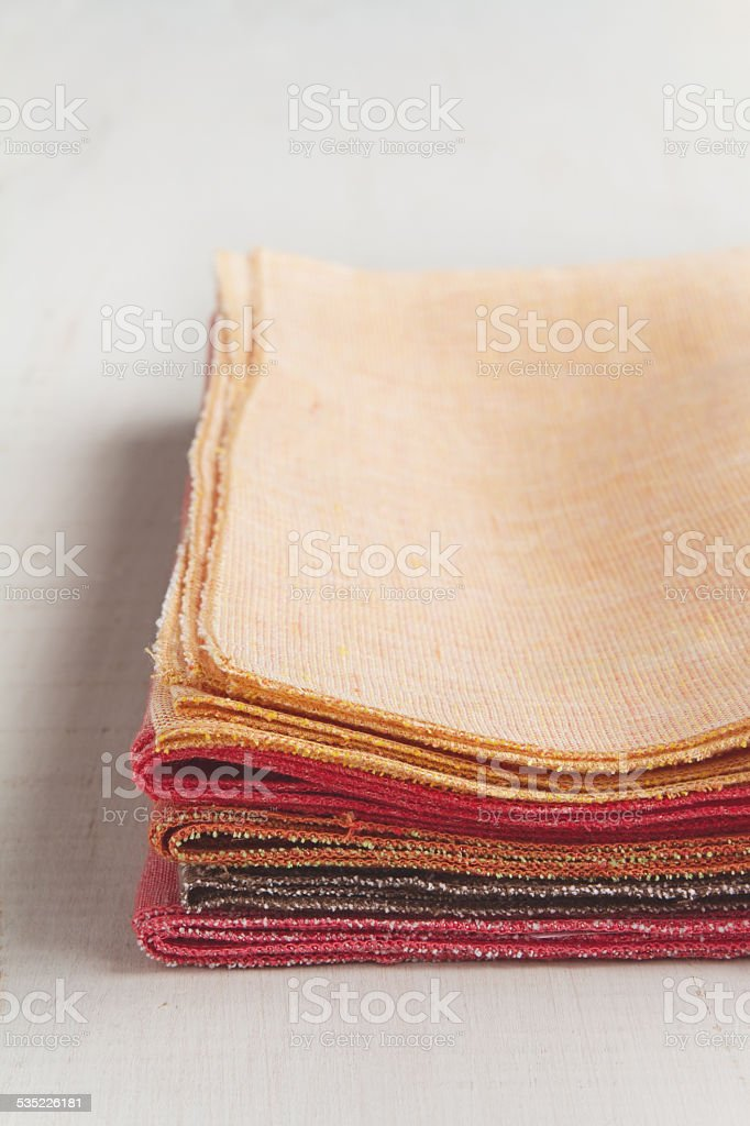 Stack of hand made colorful napkins on white background stock photo