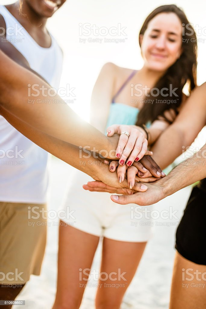Stack of hands togetherness for teamwork on the beach stock photo