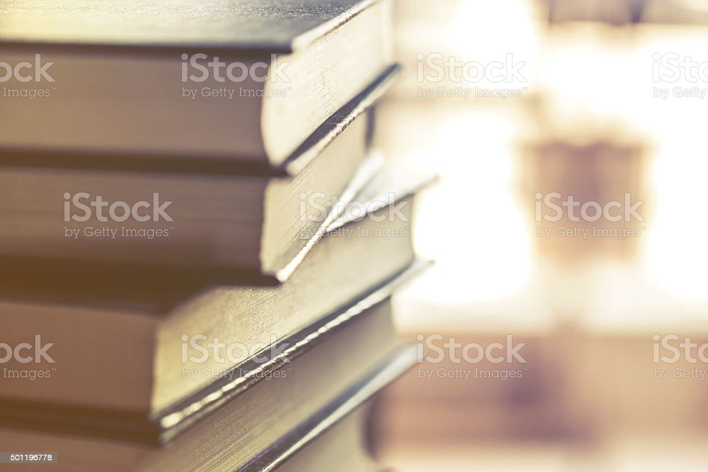 Stack of hardcover books on top of a desk stock photo