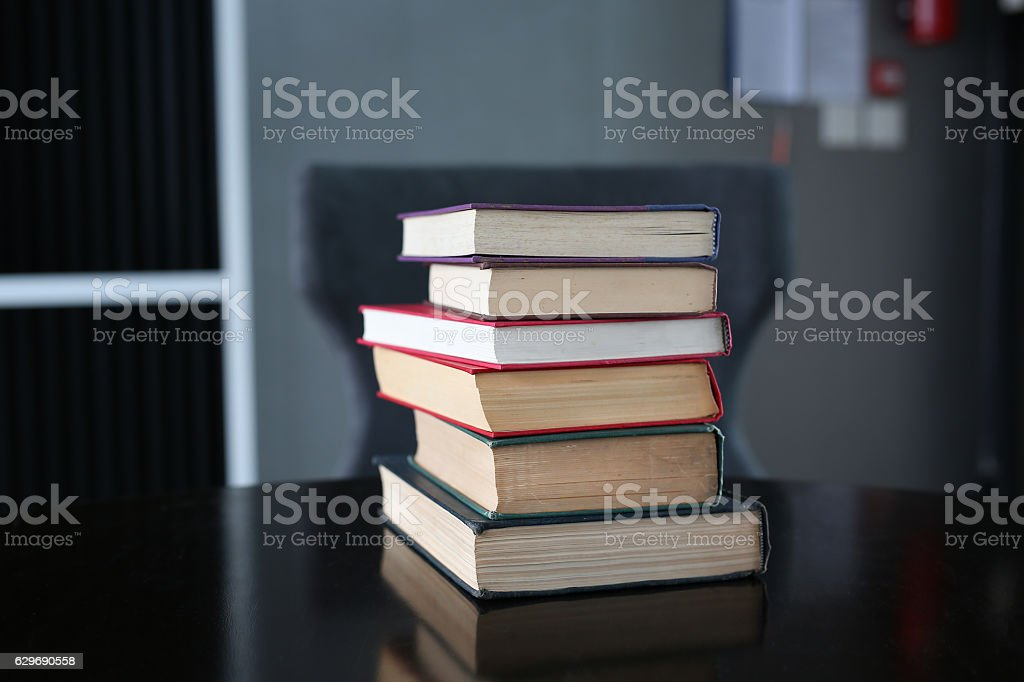 stack of hardcover books on wooden table stock photo