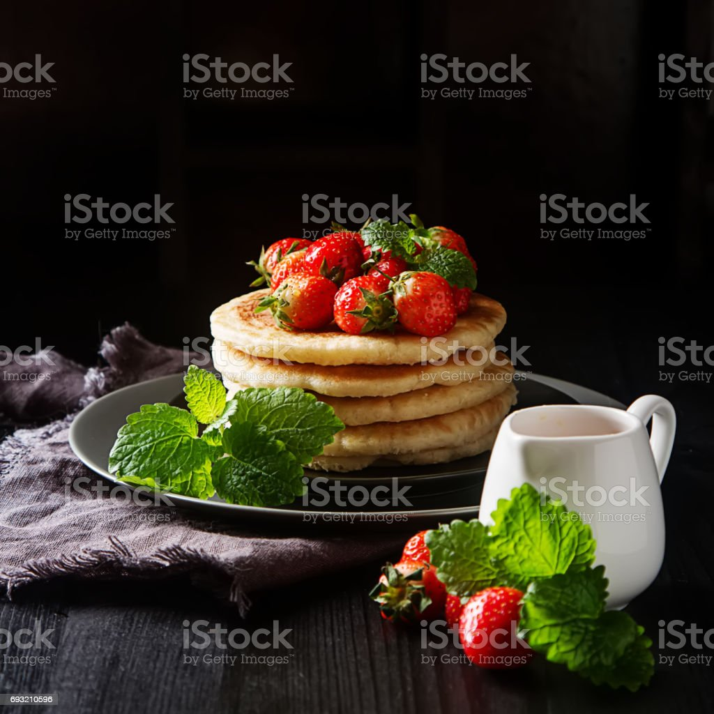 Stack of homemade Pancakes with fresh Wild Strawberries on a plate on a wooden background. stock photo