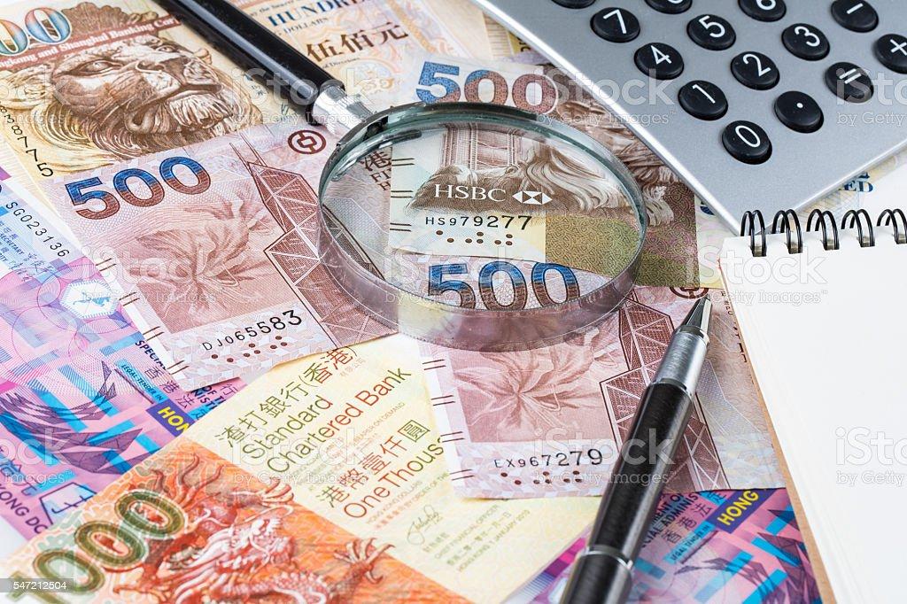Stack of Hong Kong dollar or banknotes with notepad conceptual stock photo