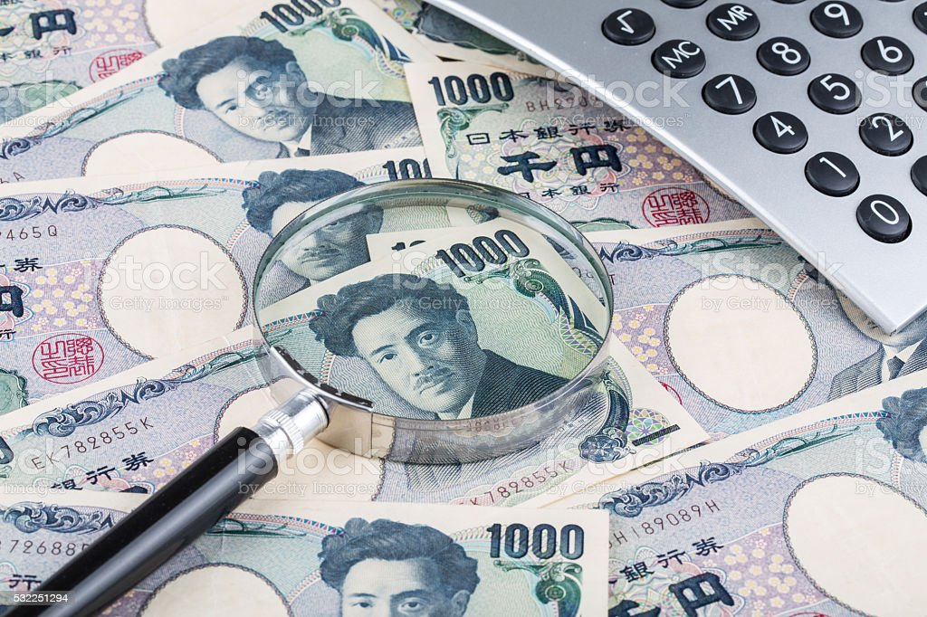 Stack of Japanese currency yen with magnifying glass and calculator stock photo