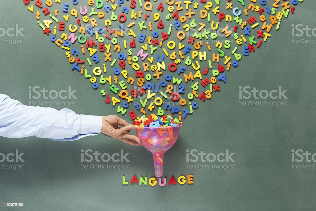 Stack of letters in chaos turning into language on blackboard stock photo