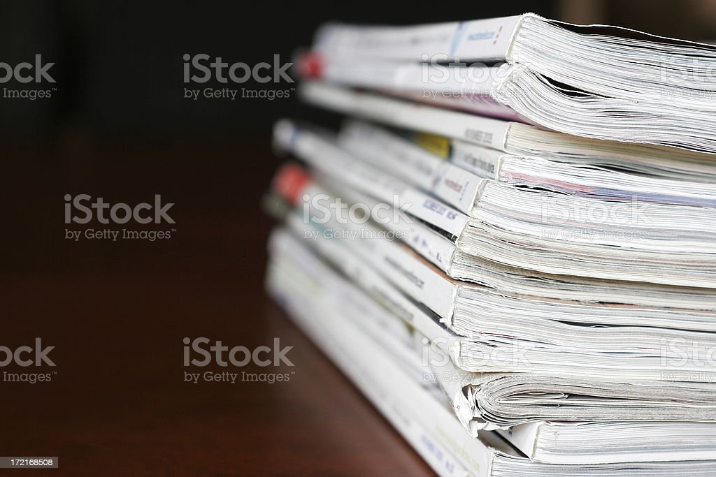 Stack of magazines over a wooden desk stock photo