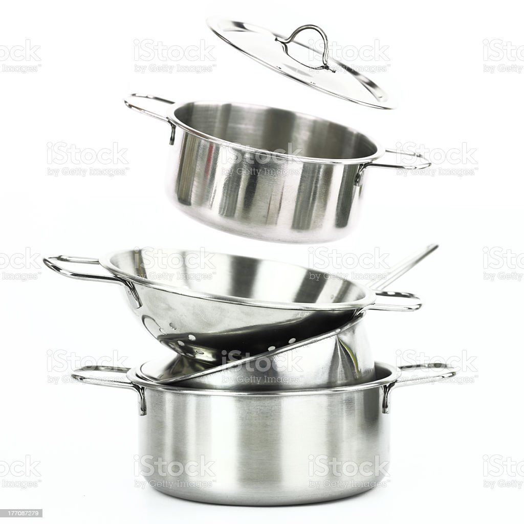 Stack of metal pots and pans on a white background stock photo