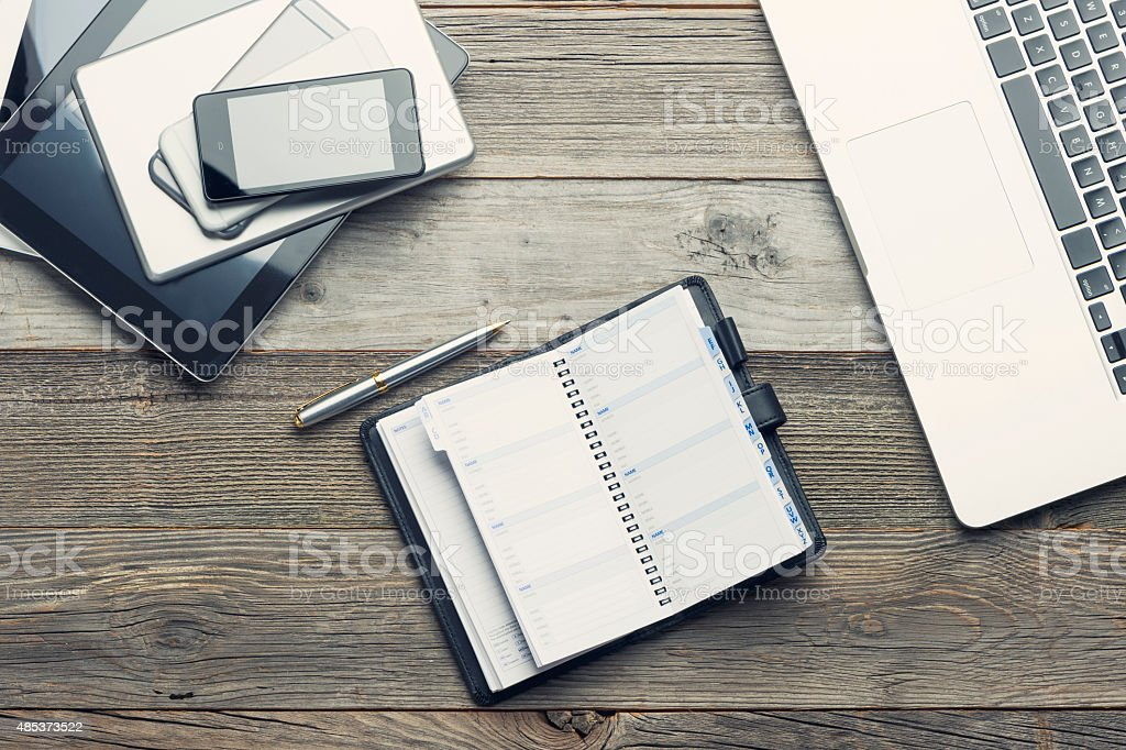 Stack of mobile devices and laptop on a wooden table. stock photo
