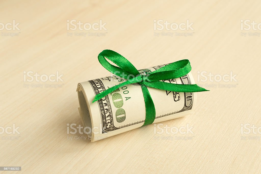 Stack of money with a ribbon. Expensive gift stock photo