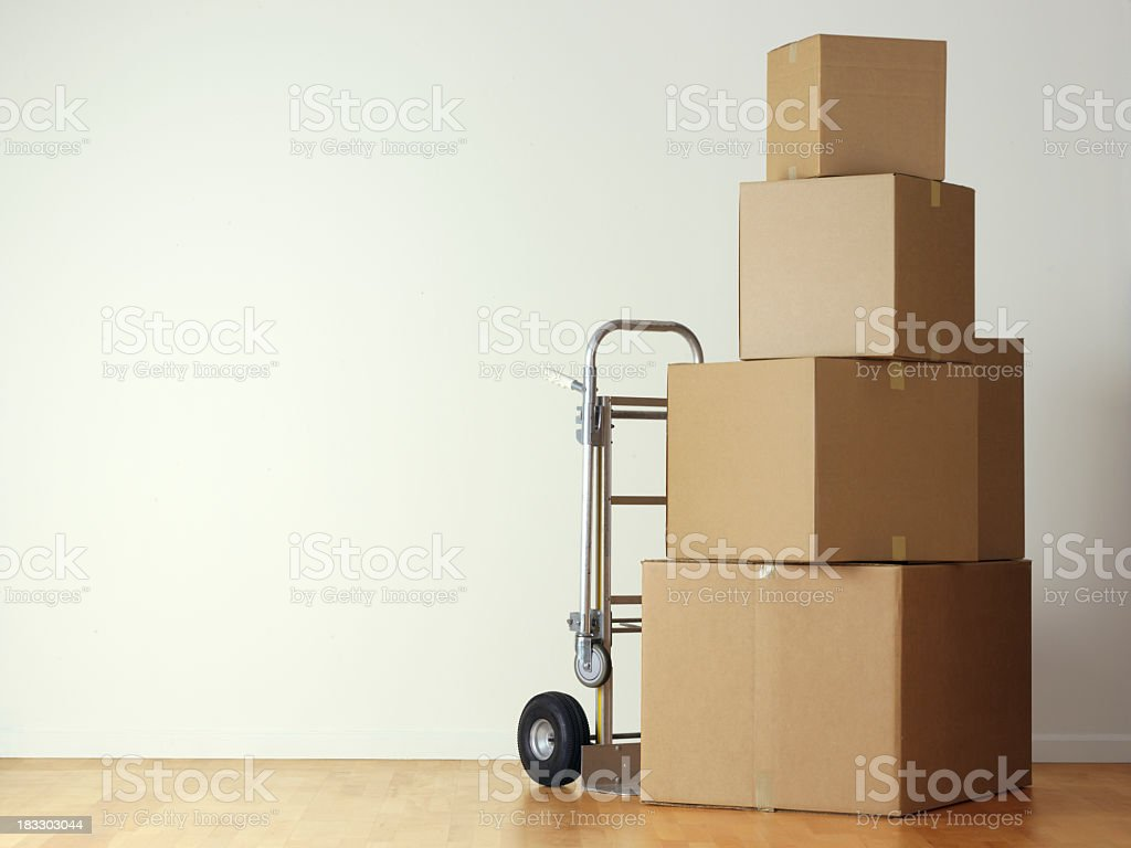 Stack of moving boxes nest to a hand truck stock photo