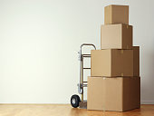 Stack of moving boxes nest to a hand truck