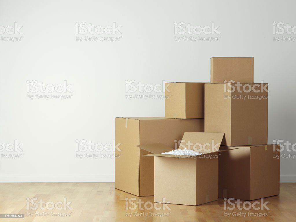 Stack of moving boxes on hardwood floor royalty-free stock photo