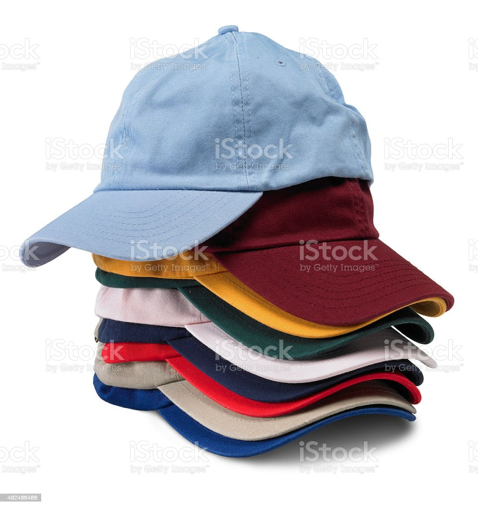 Stack of multi-colored baseball caps on white background stock photo