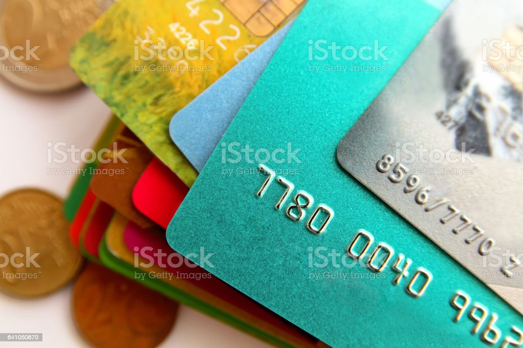 stack of multicolored credit cards and scattered coins, close up stock photo