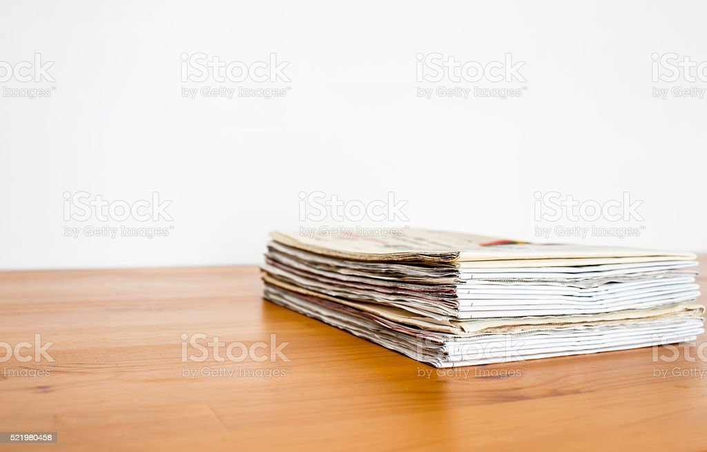 Stack of newspaper isolated on wood table stock photo