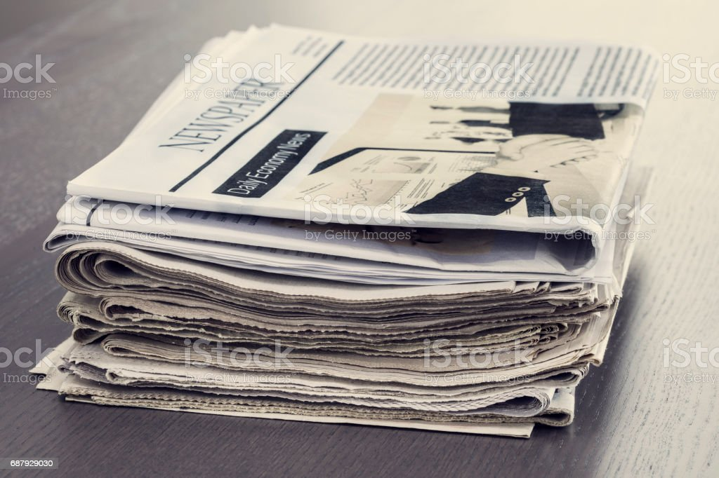 Stack of newspaper on wooden table stock photo
